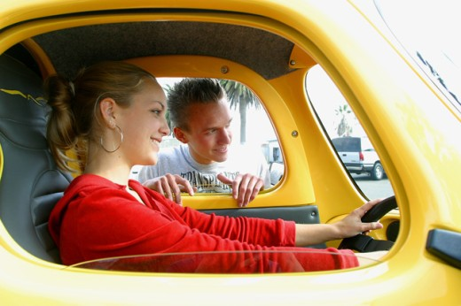 Young woman sitting in a car with a young man standing outside : Stock Photo