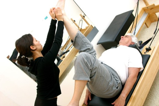 Stock Photo: 1467-1688 Female instructor helping a senior man exercise