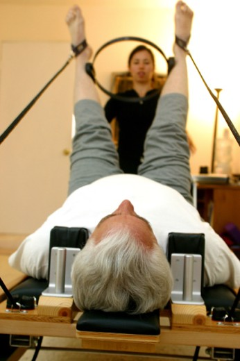 Stock Photo: 1467-1697 Female instructor helping a senior man exercise