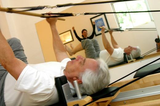 Female instructor helping a senior man exercise : Stock Photo