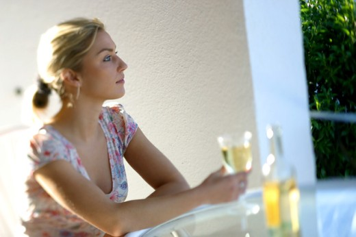 Side profile of a young woman holding a glass of wine : Stock Photo