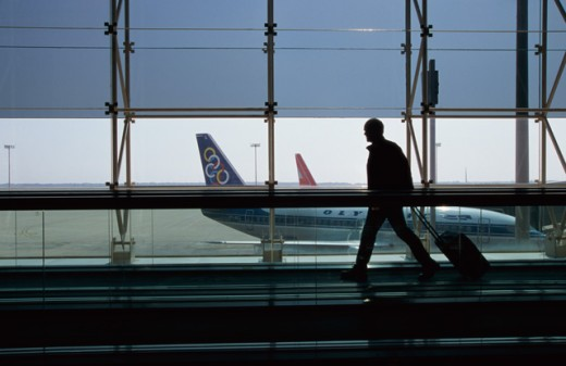Stock Photo: 1467-531 Silhouette of a man pulling his luggage through an airport
