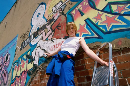 Stock Photo: 1467-712A Low angle view of a young woman leaning against a graffiti covered wall