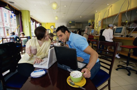 Young couple sitting in an internet cafe : Stock Photo