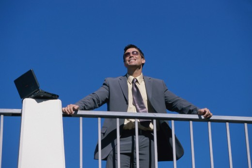 Stock Photo: 1467R-1012 Low angle view of a businessman leaning against a railing