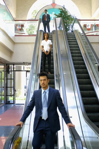 Business executives on an escalator : Stock Photo
