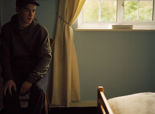 Stock Photo: 1470-128 Young man sitting near a window