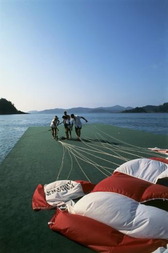 Stock Photo: 1480-W125 Four people preparing to parasail, Australia