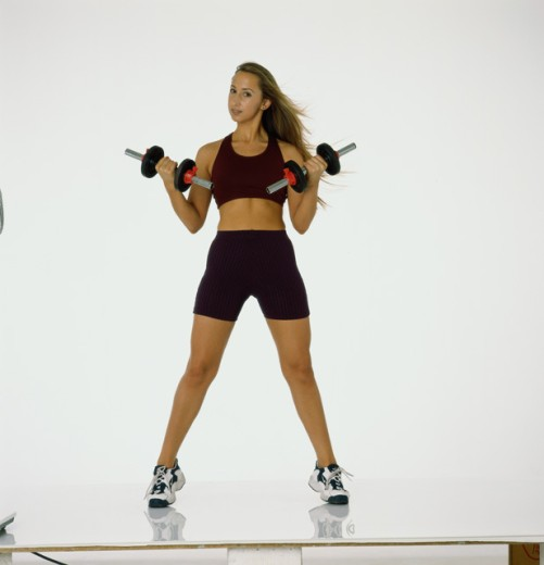 Young woman exercising with dumbbells : Stock Photo