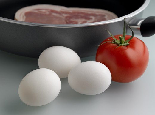 Stock Photo: 1480R-568A Close-up of a tomato with eggs and bacon in the pan