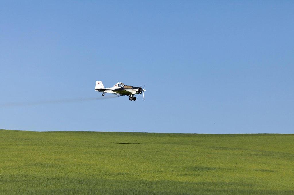 Stock Photo: 1482R-2757 USA, Oregon, Wasco, Crop sprayer over fields