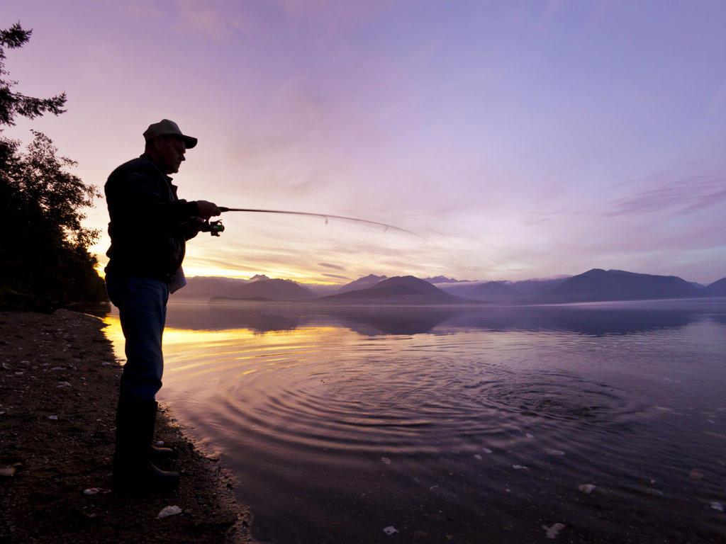 Man catching a fish at sunset, Hood Canal, Washington State, USA : Stock Photo