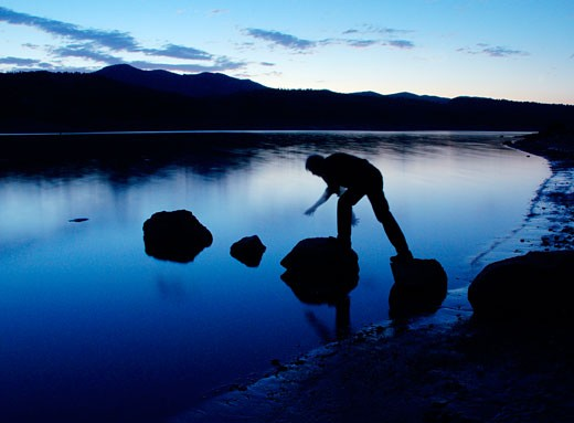 Stock Photo: 1485-376 Silhouette of a person walking on rocks on the beach