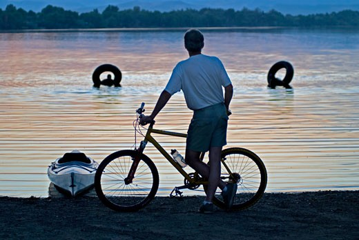 Stock Photo: 1485-378 Rear view of a man standing with his bicycle at the lakeside with two people swimming in the lake