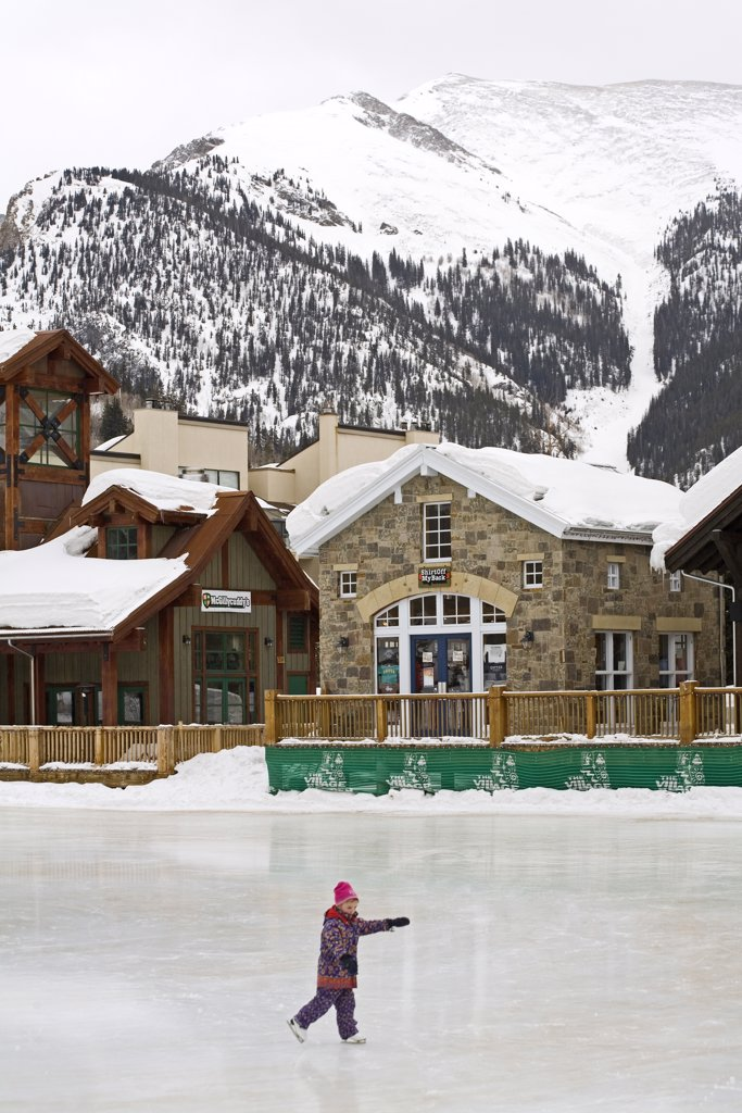 Stock Photo: 1486-10666 Person ice skating in front of ski resort, Copper Mountain Ski Resort, Colorado, USA