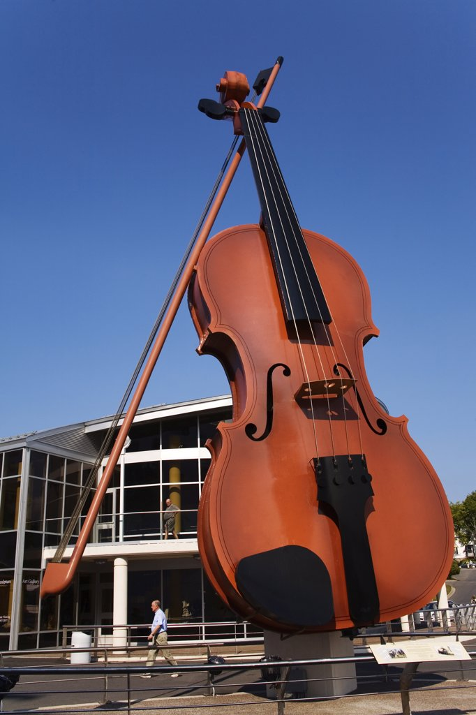 Low angle view of a sculpture of a giant fiddle, Big Ceilidh Fiddle by Cyril Hearn, Cruise Pavilion, Port of Sydney, Sydney, Cape Breton Island, Nova Scotia, Canada : Stock Photo