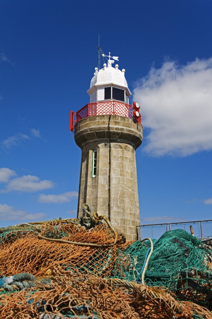 Stock Photo: 1486-11030A Fishing nets in front of a lighthouse, Dunmore East Lighthouse, Dunmore East, County Waterford, Munster Province, Ireland