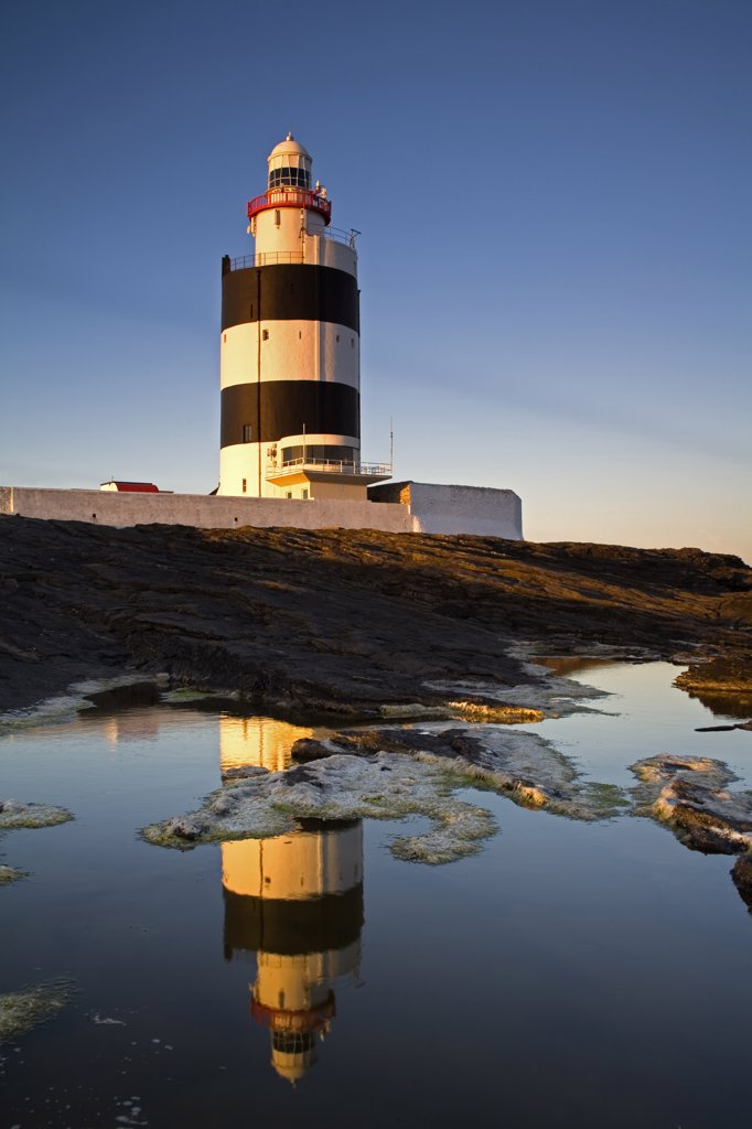 Reflection of a lighthouse in water, Hook Head Lighthouse, Hook Head, County Wexford, Leinster Province, Ireland : Stock Photo