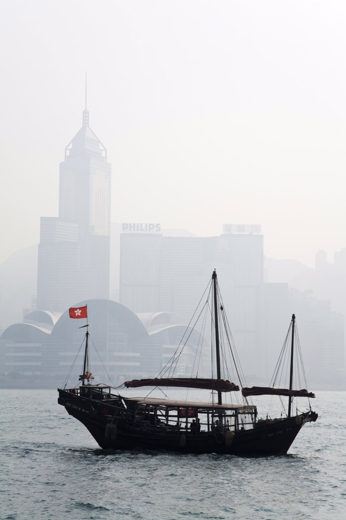 Stock Photo: 1486-11276A Junk boat in the sea with skyscrapers in the background, Victoria Harbor, Hong Kong, China