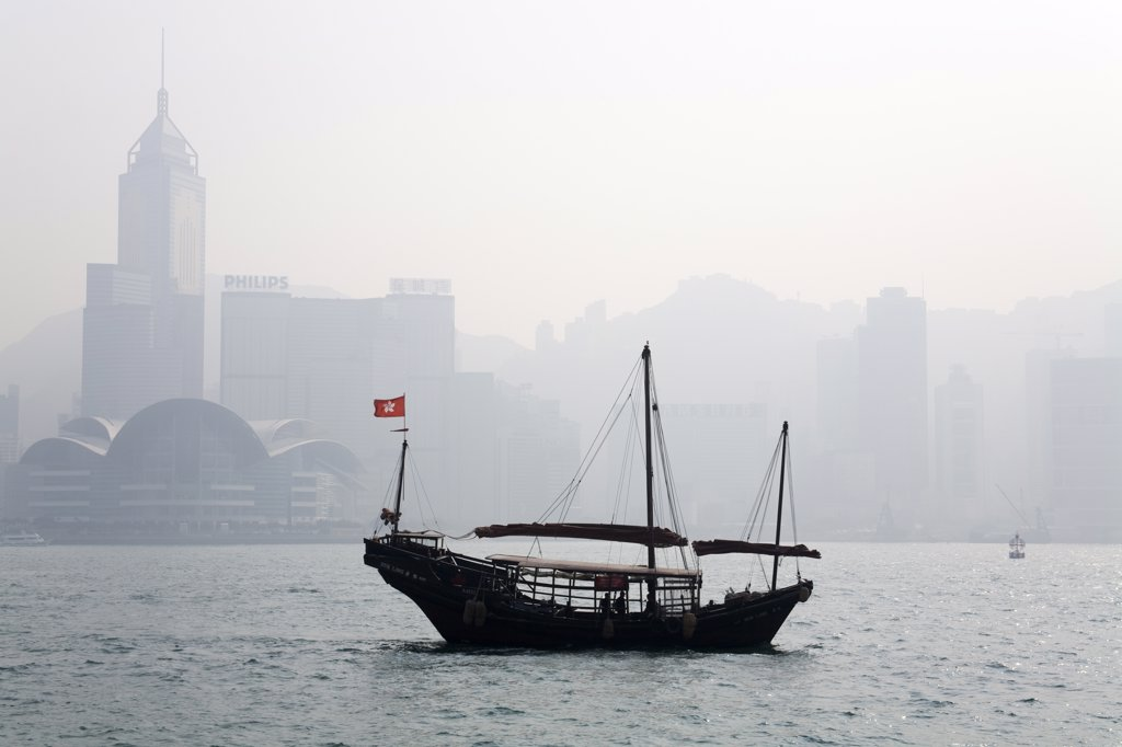 Junk boat in the sea with skyscrapers in the background, Victoria Harbor, Hong Kong, China : Stock Photo