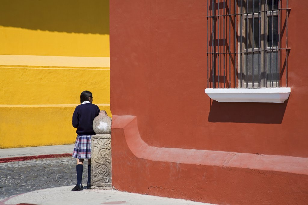 Girl standing outside a school building, Antigua Guatemala, Guatemala : Stock Photo