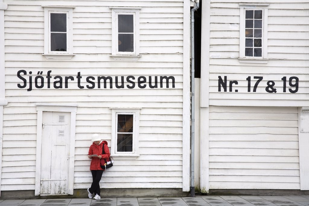 Woman leaning against the wall of a museum, Maritime Museum, Stavanger, Rogaland County, Norway : Stock Photo