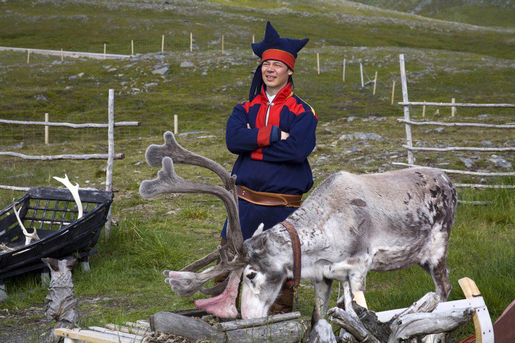 Stock Photo: 1486-11691 Sami tribal man standing beside a reindeer, Honningsvag, Mageroya Island, Nordkapp, Finnmark County, Norway