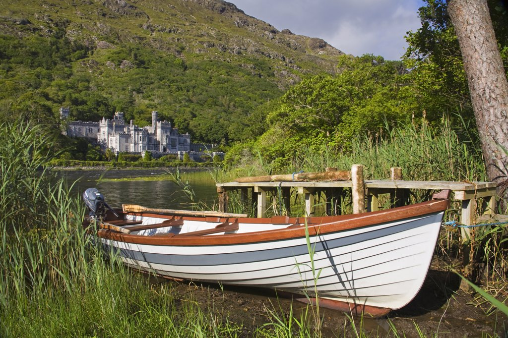 Stock Photo: 1486-11858 Boat at the lakeside with an abbey in the background, Kylemore Abbey, Lake Kylemore, Connemara, County Galway, Connacht Province, Republic of Ireland