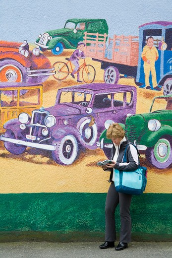 Canada, British Columbia, Vancouver, Commercial Drive, woman standing by mural by Elizabeth Hollick : Stock Photo