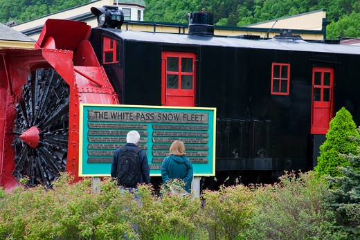 Tourists reading a signboard in front of a snowplow, White Pass and Yukon Route, Skagway, Alaska, USA : Stock Photo