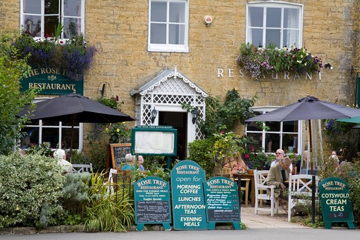 Tourists at a restaurant, Bourton-On-The-Water, Cotswold, Gloucestershire, England : Stock Photo