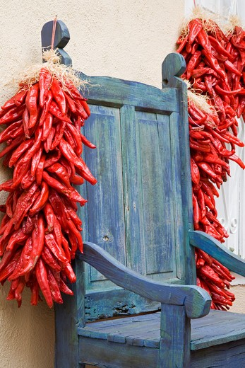 USA,New Mexico, Albuquerque, Old Town District, Antique chair and chili peppers : Stock Photo