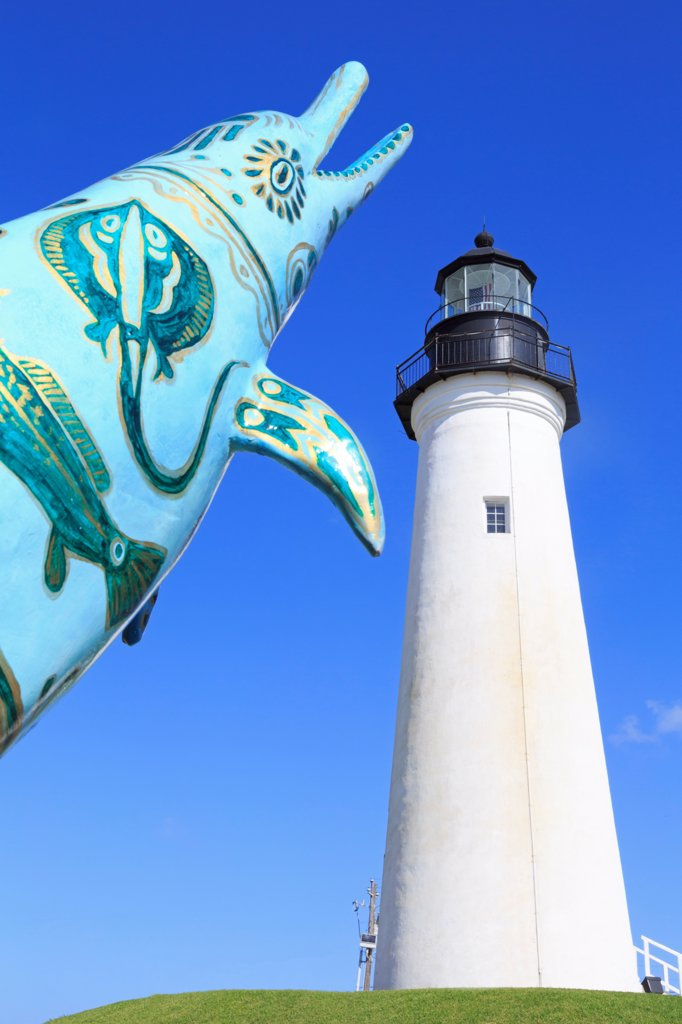 Stock Photo: 1486-16194 Sculpture of dolphin in front of a lighthouse, Point Isabel Lighthouse, Port Isabel, Texas, USA