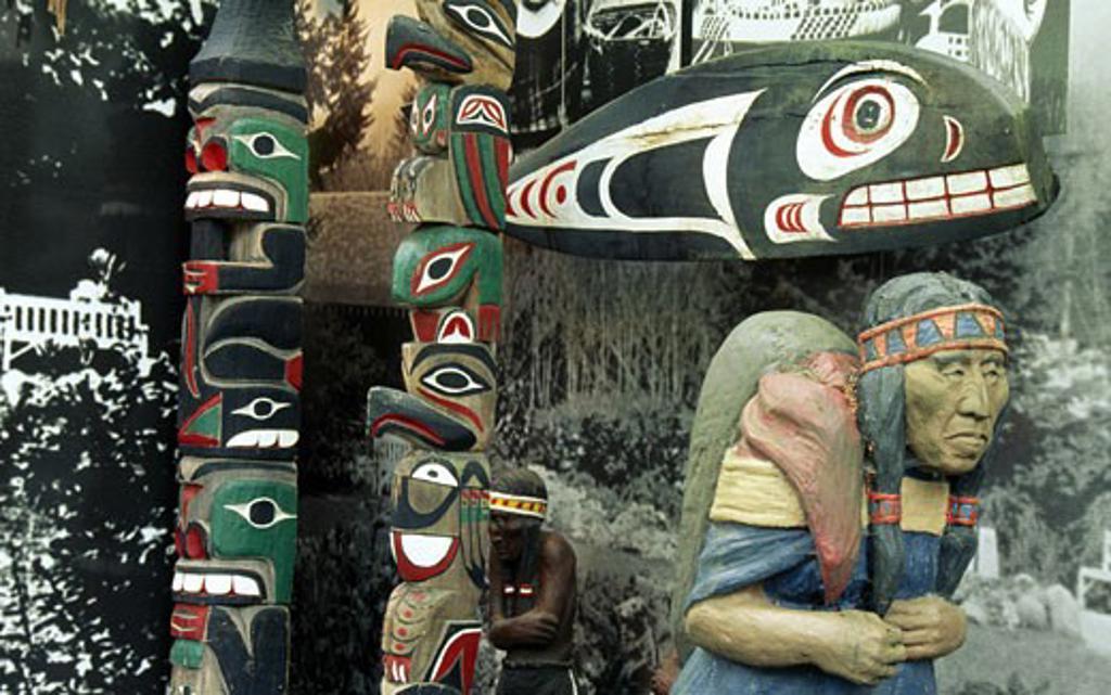 Stock Photo: 1486-1839 Canada, British Columbia, Vancouver, Capilano Suspension Bridge Park, totem poles and statue of man