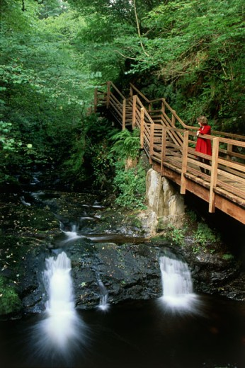 Side profile of a woman standing on a footbridge, Ess-na-Larach Waterfall, Glenariff Forest Park, County Antrim, Northern Ireland : Stock Photo