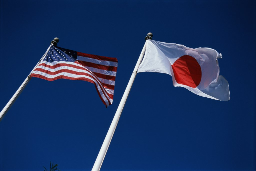 Low angle view of a Japanese and American flag fluttering side by side : Stock Photo