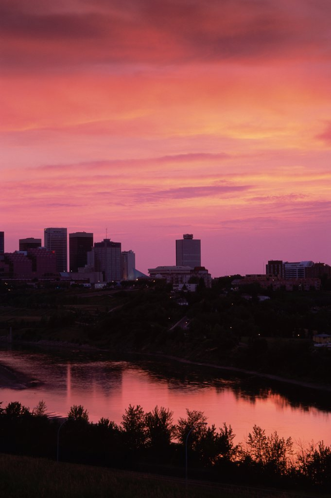 Silhouette of buildings across a river, Saskatchewan River, Edmonton, Alberta, Canada : Stock Photo