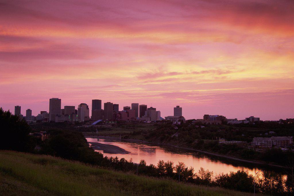 Silhouette of buildings across a river, Saskatchewan River, Edmonton, Alberta, Canada : Stock Photo