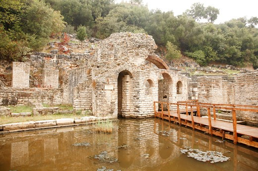 Remains of Asclepius Temple with an amphitheater in the background, Butrint, Albania : Stock Photo