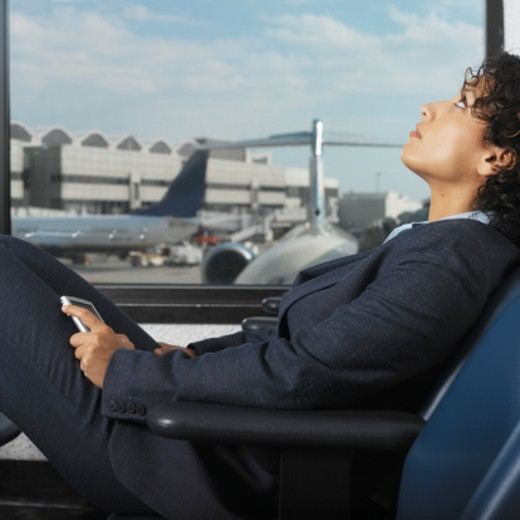 businesswoman at airport terminal resting in chair and holding pda with view of airplane through window : Stock Photo
