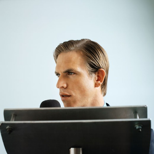 side view of a businessman looking over a podium talking into a microphone : Stock Photo