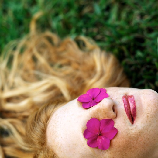 Stock Photo: 1491R-01036 elevated view of a girl lying on the ground with pink flowers on her eyes