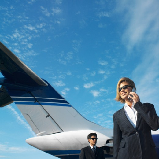 low angle view of businesswoman talking on mobile phone and businessman standing beside airplane : Stock Photo