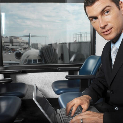businessman at airport terminal using laptop with view of airplane through window : Stock Photo