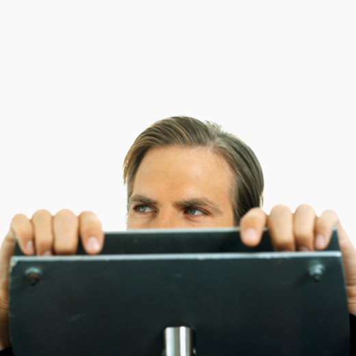 portrait of a businessman peeping over a podium : Stock Photo