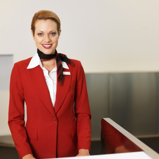 front view portrait of stewardess standing at desk : Stock Photo