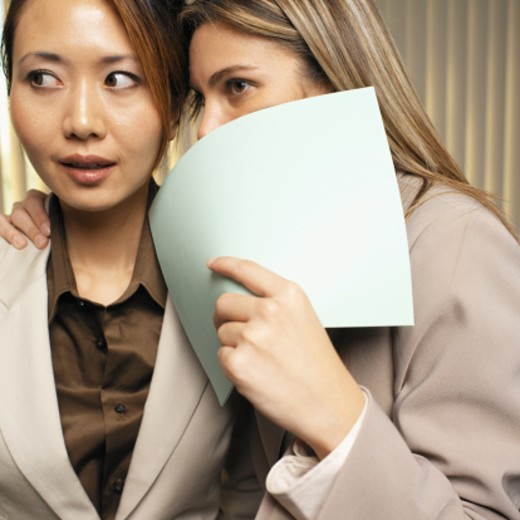two businesswoman whispering in ear : Stock Photo