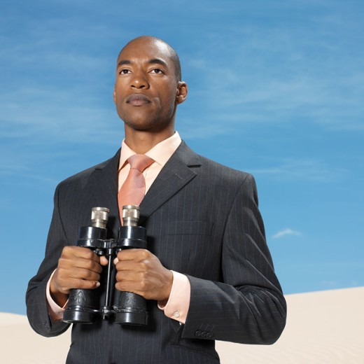 businessman in desert holding binoculars : Stock Photo