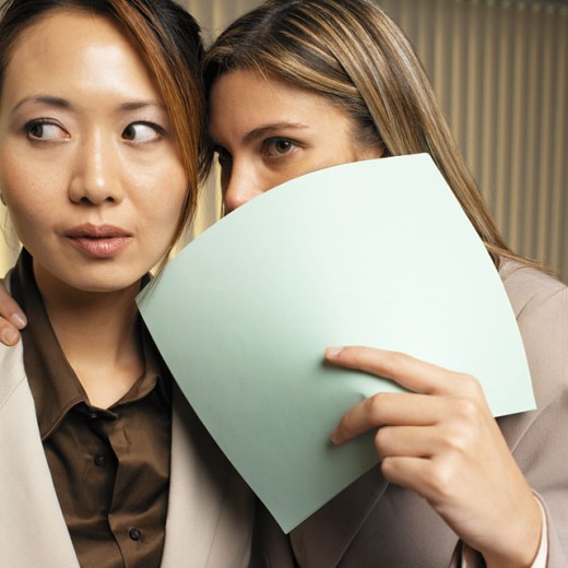 Stock Photo: 1491R-01102 two businesswoman whispering in ear close-up