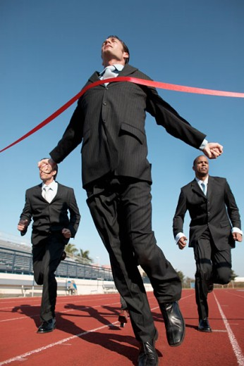 businesspeople running towards finish line low angle view : Stock Photo